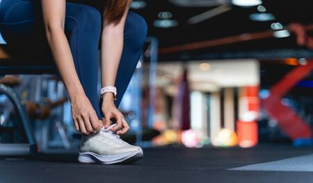 Young Asian Women are tying shoelaces To prepare before exercise and for safety, A healthy woman sitting on the bench leaning down to tie the shoelace at gym with blurback ground and copy space