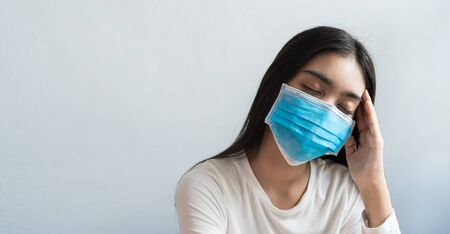 Asian women wear a mask are holding their heads because of headaches. She has a fever and migraine because of stress or sleep late, low sleep, insufficient rest in healthy concept with copy space Imagens