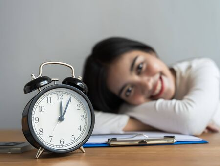 Work from home during the outbreak of the virus. Alarm Clock on the table at midnight with blur the businesswoman works from home and She was smiling after a nap. ,business concept