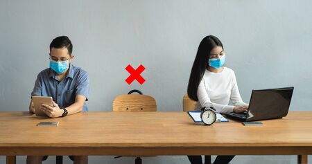 Men and women wearing masks sit apart, leaving space with red cross to keep social distancing. New normal lifestyle during the outbreak of the virus must using masked and spaced to prevent infection