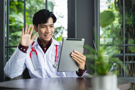 Asian Doctors are using tablets to greet patients via video call. A new normal of medical can treat, follow up illnesses and consult remote patients using the internet of things technology