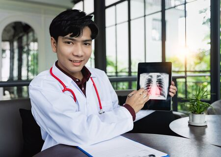 Asian Doctors are using tablets to explain about body disorders via video call. A new normal of medical can treat, follow up illnesses and consult remote patients in online  Medical and remote concept