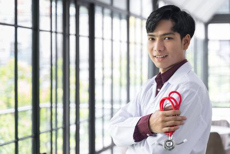 A cheerful Asian doctor stood and Crossed Arms with a stethoscope at the hospital. He looked at the camera with copy space and blur back ground