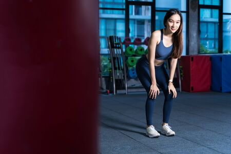 Asian Women rest during exercise. She's holding her hand at Knee with blur Racks Fitness Equipment background xhaustion and being alone at the gym sport and healthy concept
