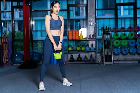 Healthy asian women are doing lifting gear, she's doing weight training exercises with Kettlebell at the fitness or gym with blur Racks Fitness Equipment background in sport and healthy concept