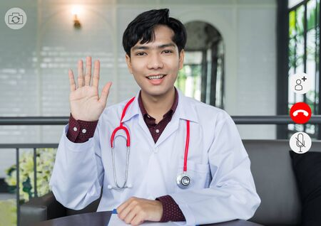 video conference screen Doctor look at camera are greet patients via video call. Doctors are using telemedicine technology to interact with patients for remote patients and keep social distancing