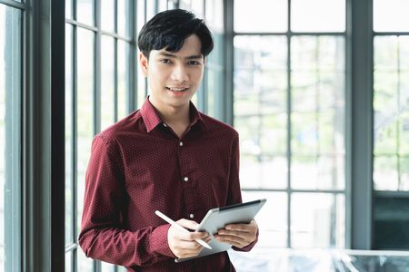Men are smiling and cheerful. Using the tablet and holding it on hand. He use tablet to work, check emails, teleconferences, or social networks. During work from home at the Home Office Imagens