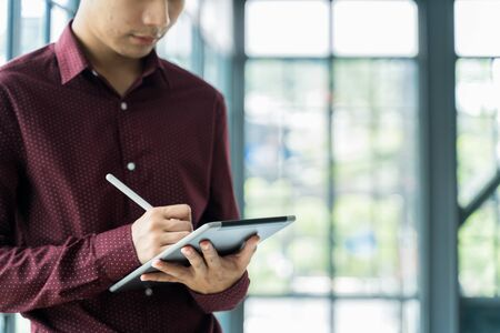 Close up Men are Using the tablet and holding it on hand. He use tablet to work, check emails, teleconferences, or social networks. During work from home at the Home Office