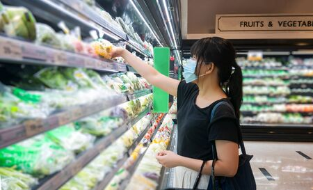 Asian women are shopping at the grocery store, holding baskets and wearing a health mask to prevent infection. She's picking vegetables from the shelves in lifestyle shopping concept Imagens