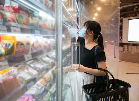 Asian women are shopping at the grocery store, holding baskets and wearing a health mask to prevent infection. She's opening the fridge to pick up the goods in lifestyle shopping concept