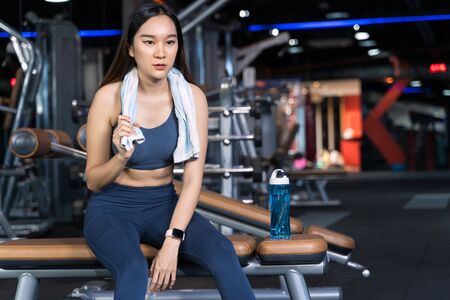 Asian women are sitting on the exercise and are holding towels with water bottles placed on their sides. She's sitting alone at the gym in sport healthy concept