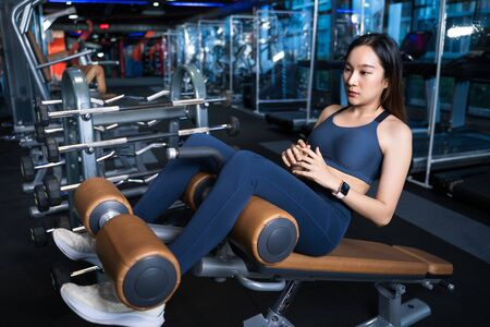 Asian women are determined to train their abdominal muscles with a sit-up pose with a sit-up device. She's creating a Six Pack to look fit in a brunette sit-up cushion in the gym in healthy concept