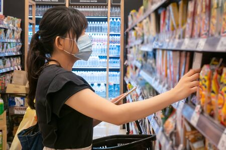 Asian women are shopping at the grocery store, holding baskets and wearing a health mask to prevent infection. She's picking goods from the shelves in lifestyle shopping concept