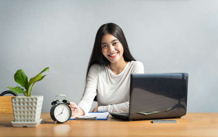 Work from home during the outbreak of the virus. Asian women sitting and working at home or online meeting, video conference and Writing data in a book in business concept at home office Imagens