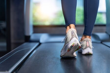 Close-up Women's feet are running on a treadmill at the gym. Women are stretching, warming up before cardio in sport and healthy concept Imagens