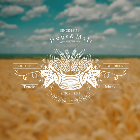 sheaf: beer label with sheaf spikelet and hop on blurred yellow field and blue sky background
