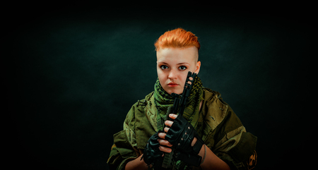 Woman with red hair in military uniform hold machine gun in darck room. Vertical photo
