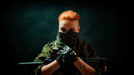 Young woman with red hair with a bandage on his face, hold machine gun on her hands in darck room. Front view Banco de Imagens