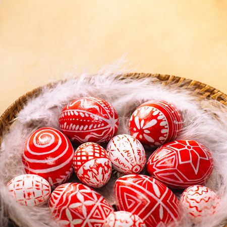 Easter red eggs with folk white pattern lay on feather into basket on retro paper, down side. Ukrainian traditional eggs pisanka and krashanka. Stockfoto