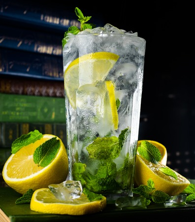 Closeup part of glass with mojito drink with lemon mint and ice beside on dark background with books.