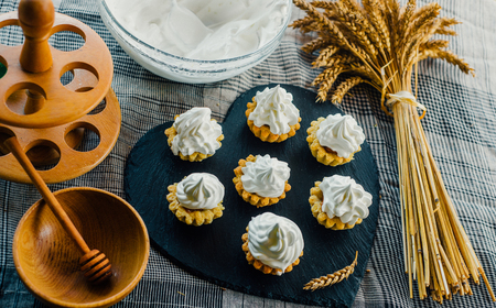 Close up tartlets with cream on black stone stand and spikelets. Top view
