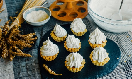 Close up tartlets with cream on black stone stand and spikelets Stock Photo