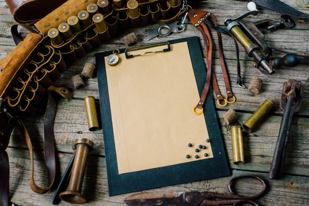 Clipboard with paper and pellets on it on old wooden background. Hunting equipment on vintage desk. Hunting belt with cartridges. Top view Archivio Fotografico