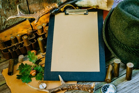 Closeup clipboard with paper for information surround hunting or tourist vintage equipment. Фото со стока