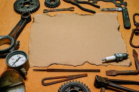 Vintage papier do informacji w centrum zardzewiałych narzędzi, kół zębatych na tle rocznika płyty pilśniowej. Szablon wyposażenia motocykla i naprawy.