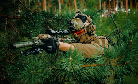 Airsoft man with optical sight gun. Soldier hidden into spruce branches on forest territory. Archivio Fotografico