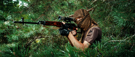 Airsoft man with optical sight russian rifle. Terrorist in arafat on face hidden in spruce branches