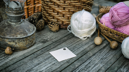 Square label on basket and ball on desk. Close up two pink balls of wool threads on vintage wood desk