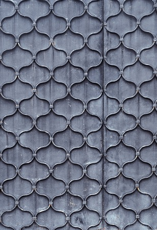 Pattern of forged waved metal rod on steel sheet. Door texture