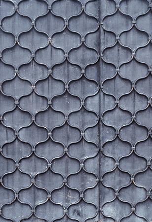 Pattern of forged waved metal rod on steel sheet. Door texture