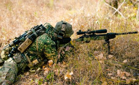 Airsoft man in uniform lay in long grass with sniper rifle. Soldier aims at the sight. Side view.