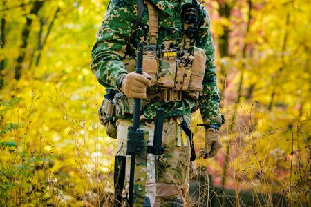 Airsoft, Part of amunition of man in uniform stand with sniper rifle on autmn forest background. Side view.
