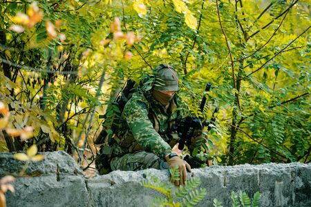 Man in uniform, climbs over the wall with sniper rifle on green forest background.