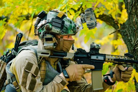 Closeup airsoft man in uniform, move with machine gun. Soldier aims at the sight. Side view.