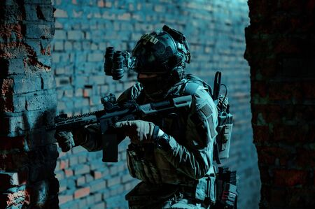 Man in uniform with machine gun and night-vision device move inside broken building. Airsoft soldier in night building.