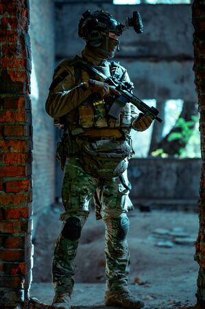 Man in uniform with machine gun and night-vision device inside broken building. Airsoft soldier in night building, beside two walls. Vertical photo.