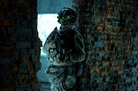 Man in uniform with machine gun and turned on night vision device stand between two brick walls inside broken building. Airsoft soldier with green light on face in night building.