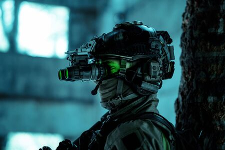 Closeup man uniform with machine gun and turned on night vision device. Airsoft soldier with green light on face in night building. Side view. Stock Photo