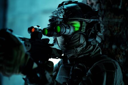 Man in uniform with machine gun and turned on night vision device beside brick wall. Closeup airsoft soldier with green light on face in night building.