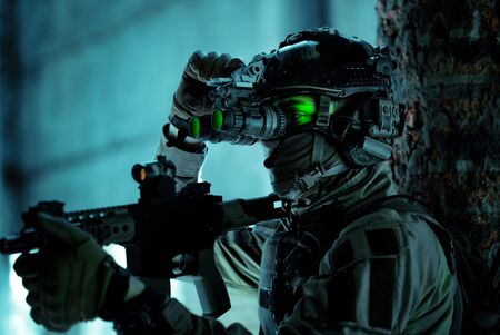 Man in uniform with machine gun and turned on night vision device inside broken building. Closeup airsoft soldier with green light on face in night building. 版權商用圖片