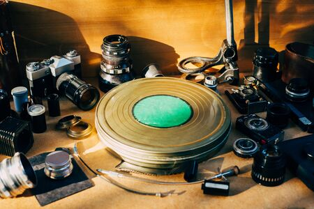 Retro photographic mockup. Metal round box from film in center and vintage photographic accessories and quipments around on Wooden Background 版權商用圖片