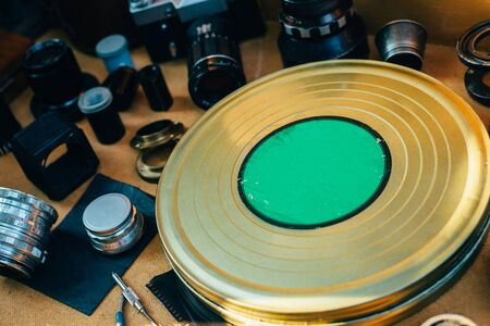 Retro mockup, metal round box from film in center and vintage photographic accessories and quipments around on Wooden Background. Side view