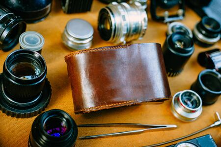 Closeup retro photographic mockup. Leather vintage box in center and vintage photographic accessories and quipments around on wooden background. 版權商用圖片