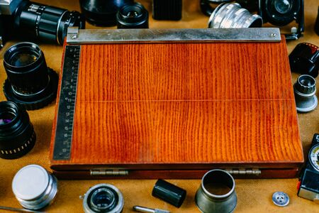 Closeup retro mockup, retro equipment for cut fotographic paper in center of retro vintage photographic accessories and quipments around on wood