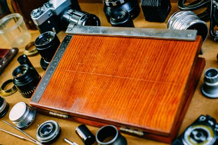 Retro mockup. Closeup old wood equipment for cut fotographic paper in center of retro vintage photographic accessories and quipments around on wooden Background. Front view 版權商用圖片