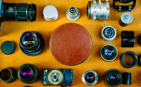 Retro photographic mockup. Closeup round leather vintage box in center and vintage photographic accessories and quipments around on wooden background. Top view